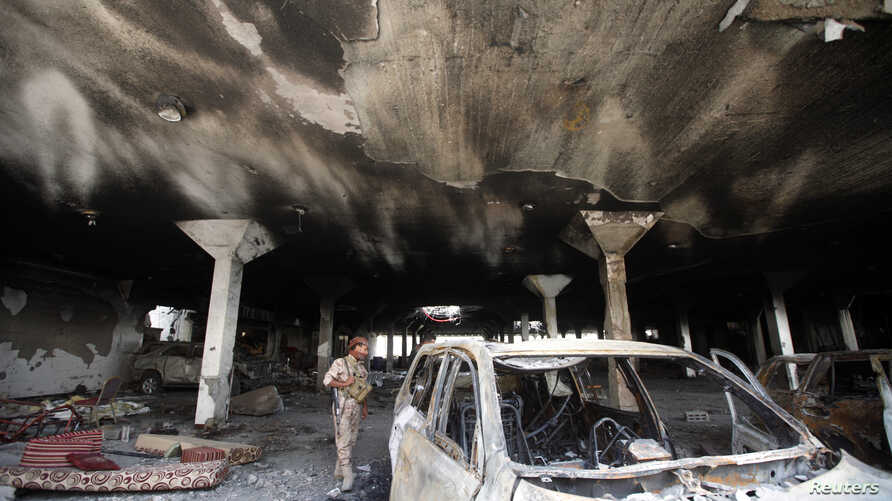 A security guard looks at a damaged car during a visit by human rights activists to a community hall that was struck by an airstrike during a funeral on October 8, in Sanaa, Yemen, October 16, 2016.