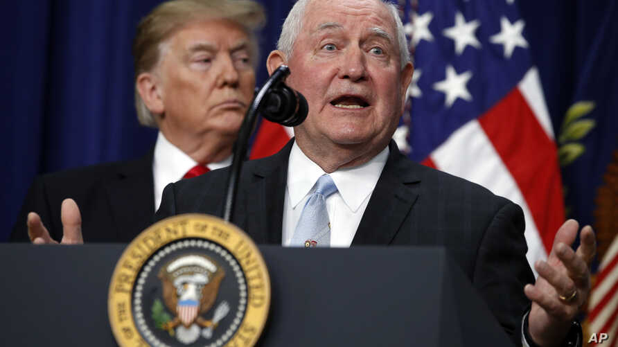 """President Donald Trump listens to Agriculture Secretary Sonny Perdue during a signing ceremony for H.R. 2, the """"Agriculture Improvement Act of 2018,"""" in the Eisenhower Executive Office Building, on the White House complex, Dec. 20, 2018, in Washingto"""