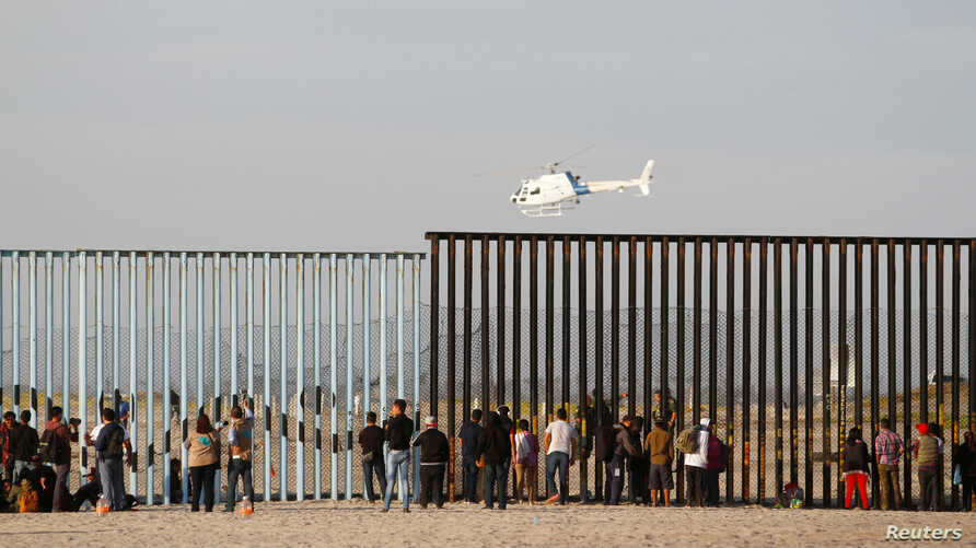 Migrants, part of a caravan of thousands trying to reach the U.S., look through the border fence between Mexico and the United States after arriving in Tijuana, Mexico, Nov. 13, 2018.