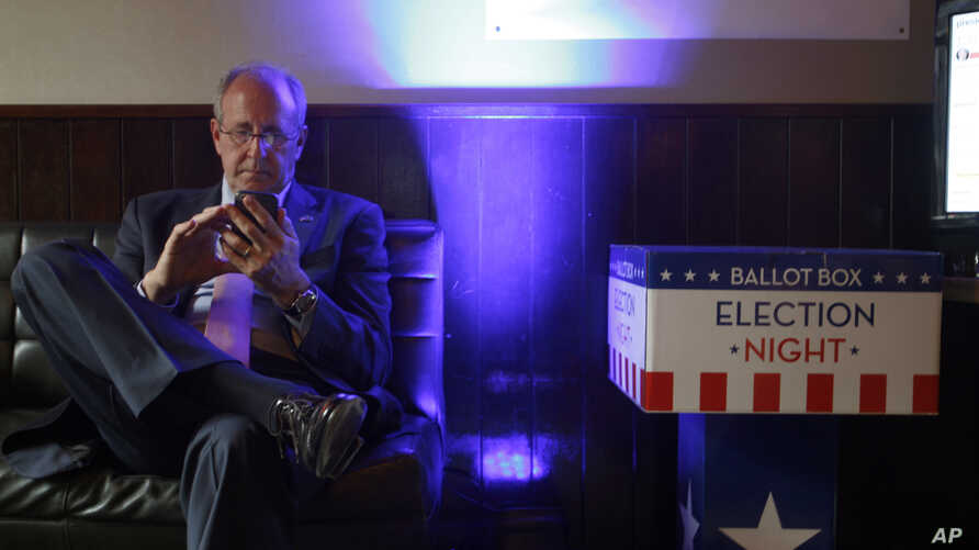 Mark Gilbert, U.S. ambassador to New Zealand, checks election results on his phone in Wellington, New Zealand,  Nov. 9, 2016. Gilbert was appointed by President Barack Obama and has been told by the Trump transition team to be out by Jan. 20.
