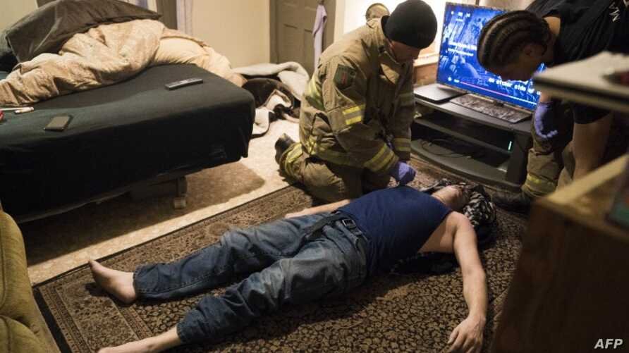 FILE - Firefighter Jim Terrero (R) and Corey Joy, of the Manchester Fire Department, assess the condition of a 35-year-old man who had overdosed on heroin March 28, 2018 in Manchester, New Hampshire.