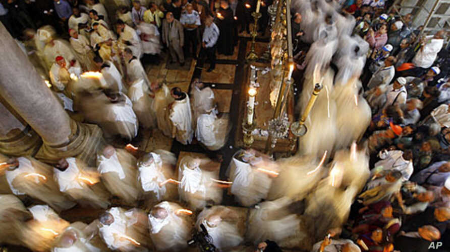 Members of the Catholic clergy hold candles as they take part in a procession at the end of Easter Mass in the Church of the Holy Sepulchre in Jerusalem's Old City April 8, 2012.