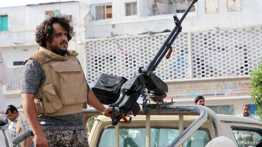 A fighter of the southern Yemeni separatists mans a machine gun mounted on a military vehicle securing an anti-government protest in Aden, Yemen, Jan. 28, 2018.