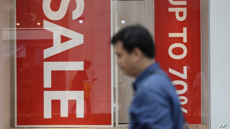 A man passes by sale signs at a shopping district in Seoul, South Korea, July 13, 2017. Bank of Korea says South Korea's economy is likely to expand 2.8 percent this year thanks to strong exports.