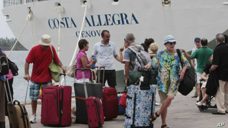 Passengers of the Costa Allegra cruise ship wait to board on a ferry at Victoria's harbor, Seychelles, March 1, 2012.