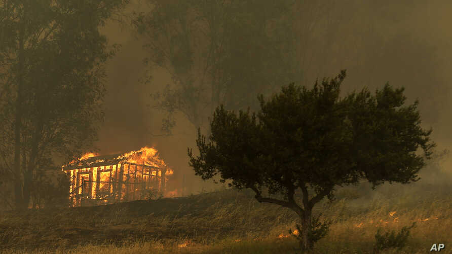 Fire engulfs a structure during a wildfire May 15, 2014, in Escondido, California.