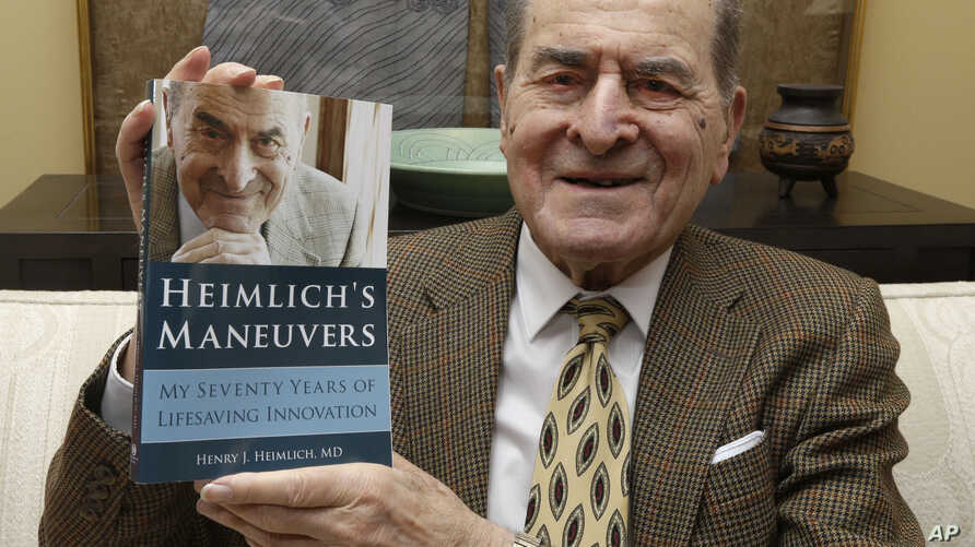 Dr. Henry Heimlich holds his memoirs prior to being interviewed at his home in Cincinnati, Feb. 5, 2014. He died Dec. 17, 2016, at a hospital in Cincinnati after suffering a heart attack days earlier. He was 96.
