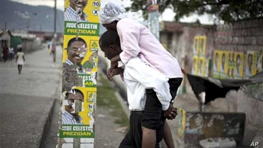 A man carrying a woman with cholera symptoms walks past campaign posters of presidential candidate Jude Celestin in Port-au-Prince (File)