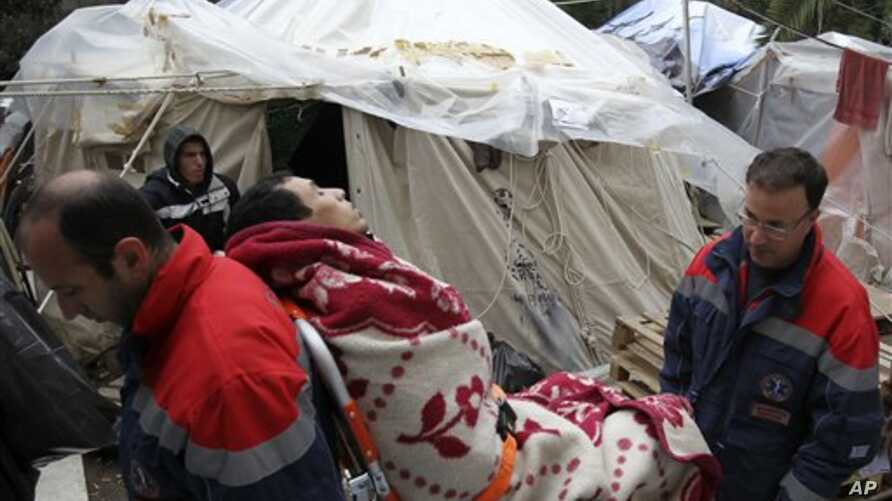 An immigrant from North Africa is carried away by paramedics at the Hypatia mansion in Athens, March 1, 2011