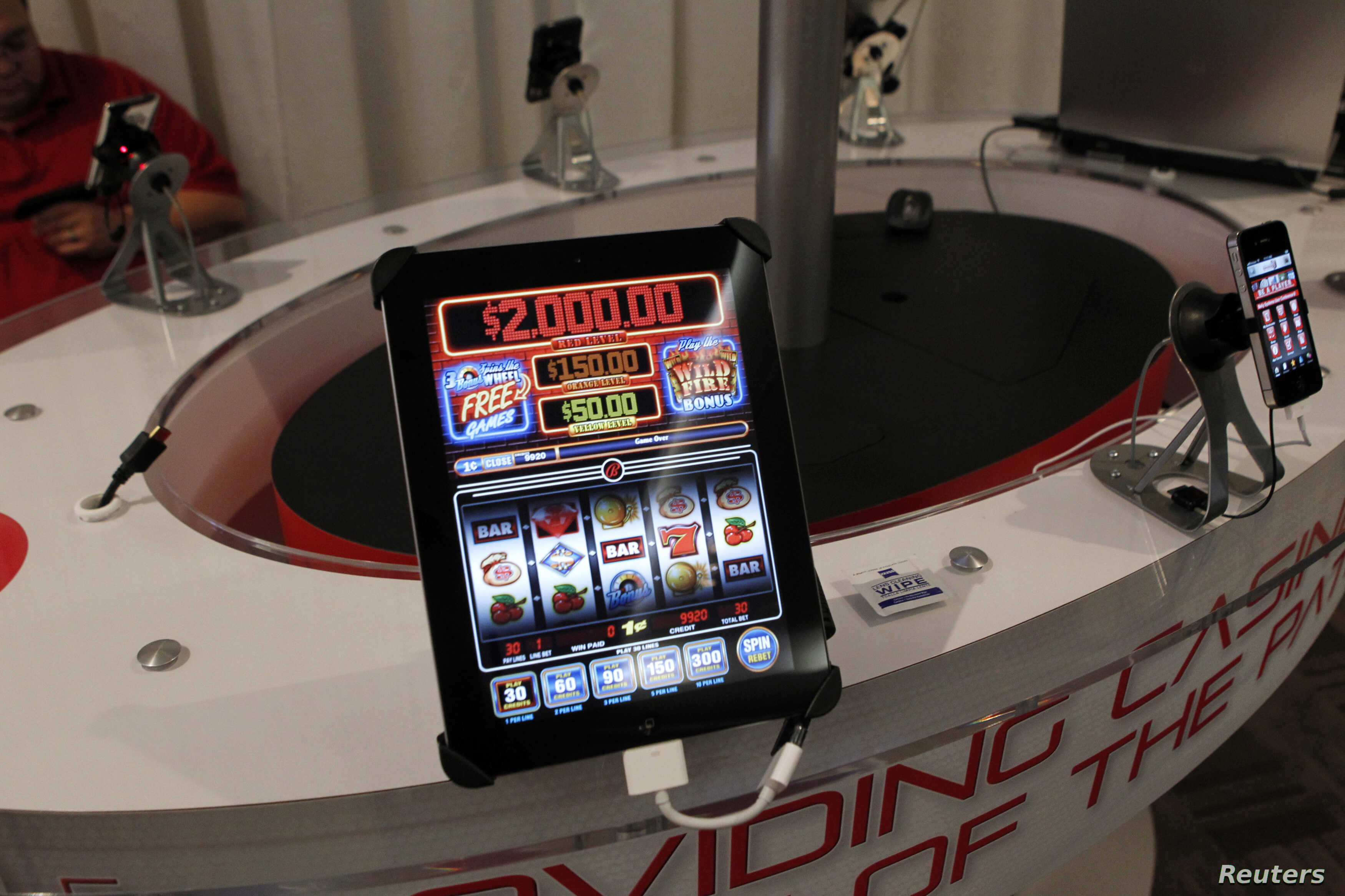"""San Manuel Indian Bingo and Casino's online gambling app """"Code Red"""" is demonstrated in the exhibitors room at the GiGse online gaming convention in San Francisco, April 24, 2012."""