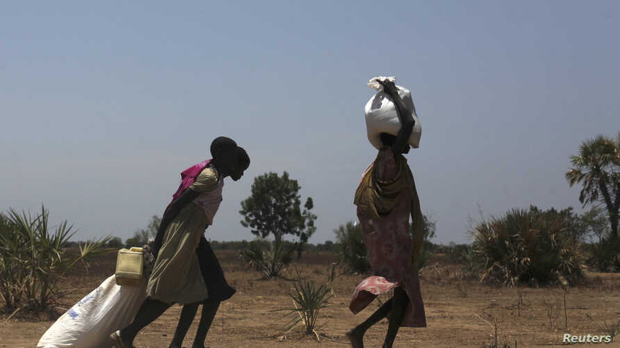 Women carry food at a food distribution site in Nyal, Unity State, Apr.1, 2014.