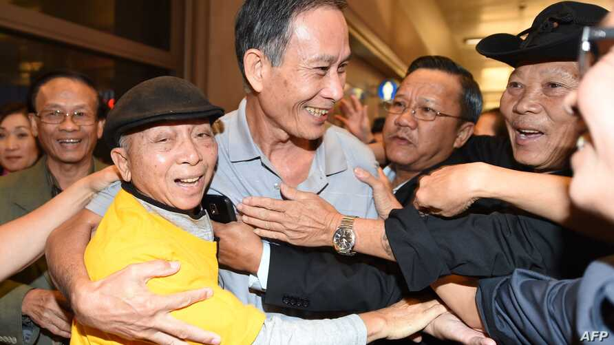 "Freed Vietnamese dissident Nguyen Van Hai (C) is greeted upon arrival at Los Angeles International Airport on October  21, 2014 in Los Angeles, California.  The Vietnamese blogger, also known by his pen name ""Dieu Cay,"" was handed a 12-year prison se"