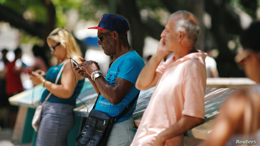 Cubans check their phones at an internet hotspot in Havana, Cuba, Aug. 10, 2018. A day of free, expanded internet was provided by the state-run telecommunications company  on Aug. 14, 2018.