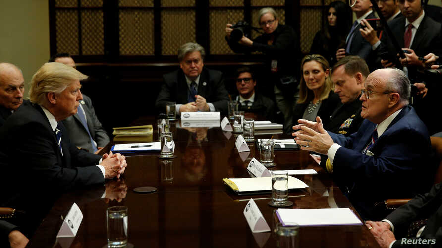 U.S. President Donald Trump listens to former New York City Mayor Rudy Giuliani during a meeting with cybersecurity experts in the Roosevelt Room of the White House in Washington, Jan. 31, 2017.