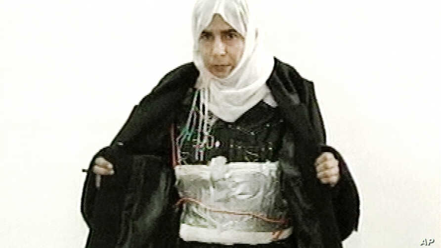 FILE - This image made from television shows Iraqi Sajida Mubarek Atrous al-Rishawi opening her jacket and showing an explosive belt as she confesses on Jordanian state-run television to her failed bid to set off an explosives belt inside one of the