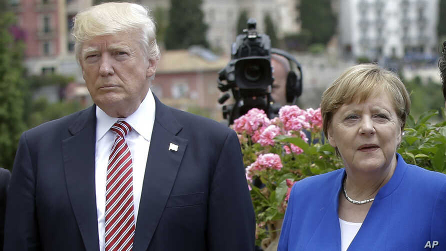 FILE - US President Donald Trump is flanked by German Chancellor Angela Merkel during the G7 meeting in Taormina, Italy, May 26, 2017.