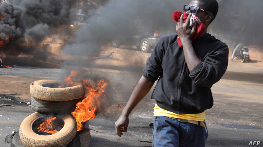 A man holds a hat over his mouth as black smoke billows from tires set on fire in Niamey after police fired teargas to disperse a banned opposition demonstration in the Niger capital, Jan. 18, 2015.