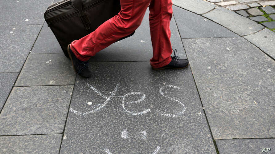 A person walks by a message left by a member of the 'Yes' campaign written on a pavement, in Edinburgh, Scotland,  Sept. 17, 2014.
