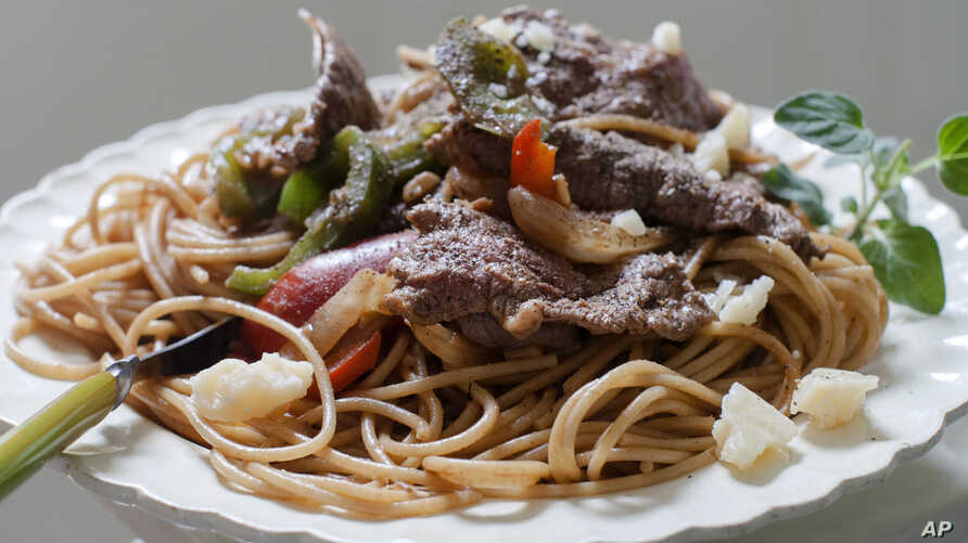 FILE - A dish of steak and cheese pasta is ready to eat in Concord, N.H., June 9, 2014. Two major studies in 2018 provided more fuel for the debate around carbs and fats, yet failed to offer a resolution to the polarizing matter of the best way to lo
