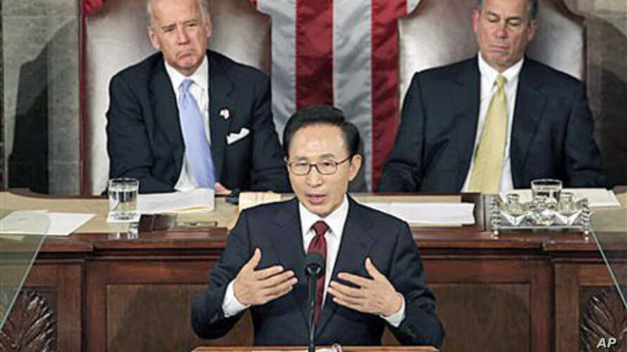 South Korean President Lee Myung-bak speaks to a joint meeting of Congress as Vice President Joe Biden (L) left, and Speaker of the House John Boehner (R) look on at the Capitol in Washington, October 13, 2011.