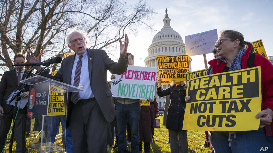 Sen. Bernie Sanders, I-Vt., joins protesters outside the Capitol as Republicans in the Senate work to pass their sweeping tax bill, a blend of generous tax cuts for businesses and more modest tax cuts for families and individuals, on Capitol Hill in