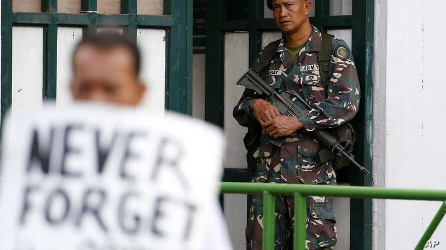 A soldier watches demonstrators protest President Rodrigo Duterte's Martial Law declaration for the southern Mindanao region, July 7, 2017, outside of the Philippine armed forces headquarters in Quezon city northeast of Manila, Philippines.