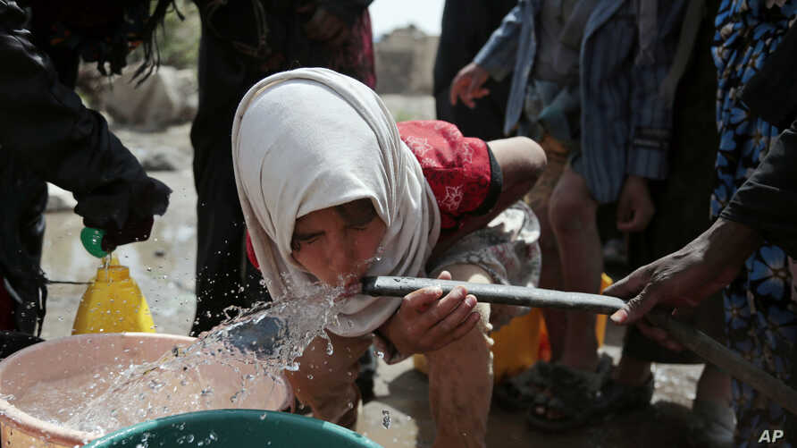 A girl drinks water from a well that is allegedly contaminated with cholera bacteria, on the outskirts of Sanaa, Yemen, Wednesday, July 12, 2017. The U.N. health agency said Tuesday that plans to ship cholera vaccine to Yemen are likely to be shelved