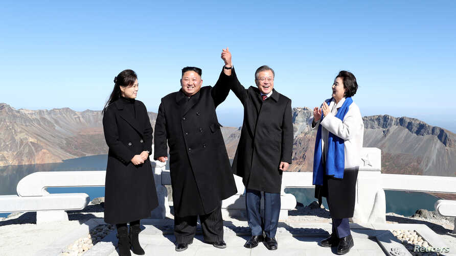 South Korean President Moon Jae-in and North Korean leader Kim Jong Un pose for photographs on the top of Mt. Paektu, North Korea, Sept. 20, 2018.