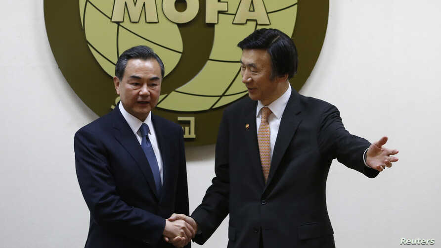 South Korean Foreign Minister Yun Byung-se gesture to his Chinese counterpart Wang Yi (L)  before their meeting at the Foreign Ministry in Seoul, May 26, 2014.