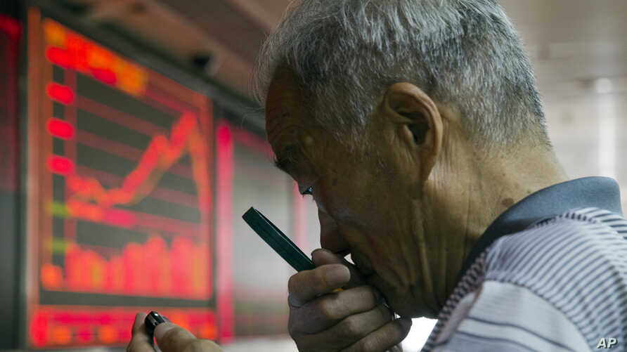 A Chinese investor uses a magnifying glass to look at his mobile phone screen as he monitors stock prices at a brokerage house in Beijing, China, July 9, 2015.
