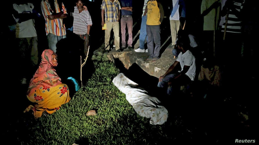 Relatives and friends gather around the covered body of Zedi Feruzi, the head of opposition party UPD, in Bujumbura, Burundi, May 23, 2015.