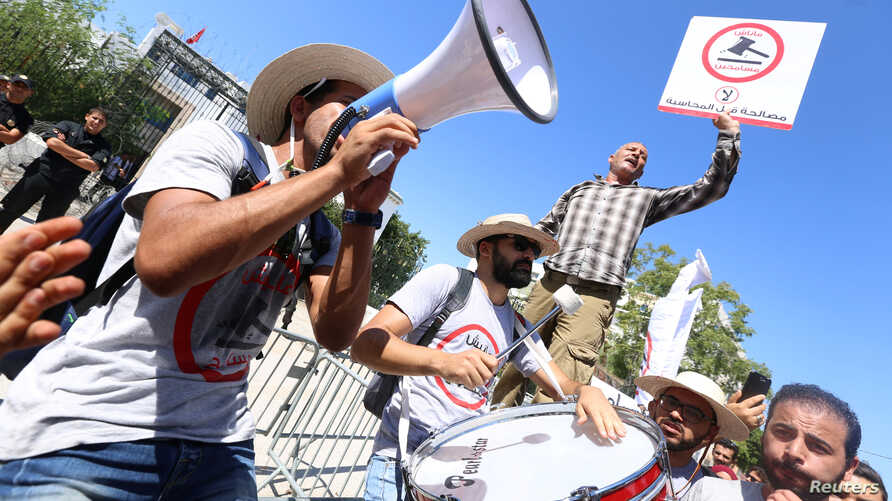 A protester hits a drum during a demonstration against a bill that would protect those accused of corruption from prosecution in front of the Assembly of the Representatives of the People headquarters in Tunis, Tunisia, Sept. 13, 2017. The sign reads