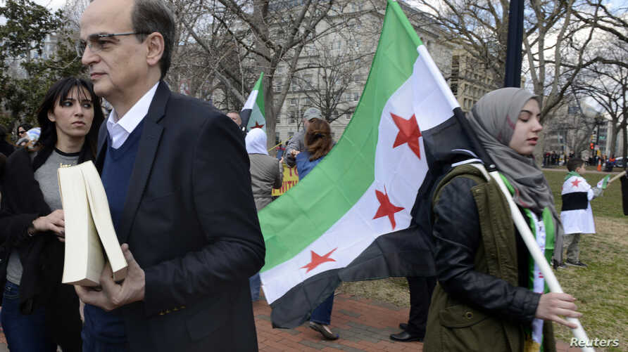 Chief Syrian Opposition Coalition negotiator Hadi al-Bahra (L) awaits his turn to address dozens of protestors gathered to mark the third anniversary of the Syrian revolution, in Lafayette Park, across from the White House in Washington, March 15, 20