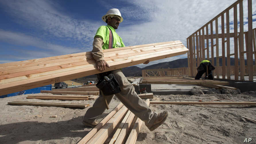 Construction worker Miguel Fonseca carries lumber as he works on a house frame for a new home, Nov. 16, 2012, in Chula Vista, Calif.