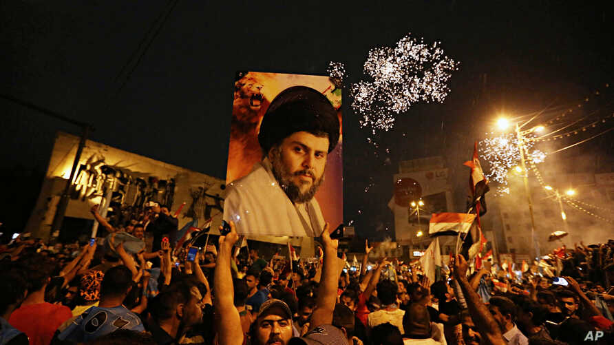 Followers of Shi'ite cleric Muqtada al-Sadr, seen pictured on the poster, celebrate in Tahrir Square, Baghdad, Iraq, early Monday, May 14, 2018.