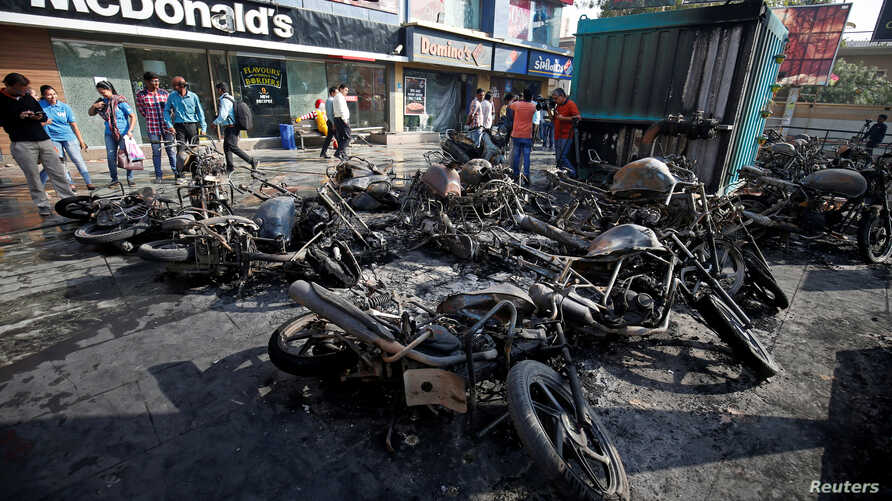 Burnt vehicles, set on fire Tuesday night following a protest by people belonging to Rajput community against the release of the upcoming Bollywood movie 'Padmaavat,' are seen outside a multiplex in Ahmedabad, India Jan. 24, 2018.
