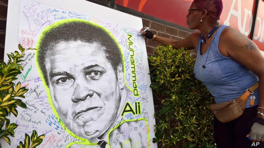 A woman signs a mural of boxing great Muhammad Ali in the Brooklyn Borough of New York outside of a gathering hosted by director Spike Lee, June 4, 2016.