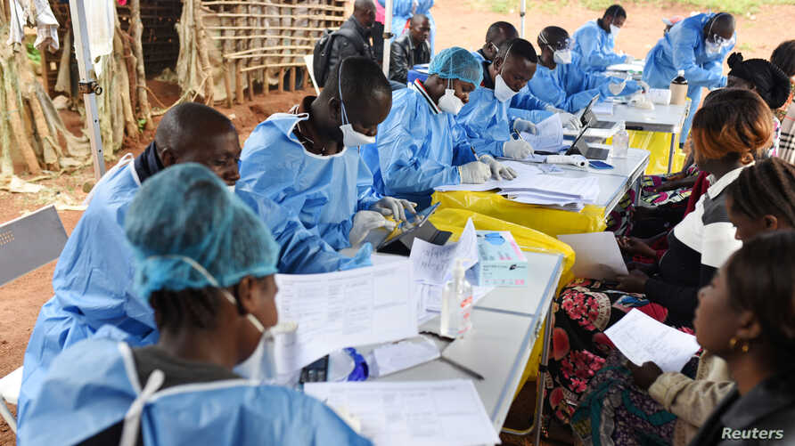 FILE - Congolese health workers register people and take their temperatures before they are vaccinated against Ebola in the village of Mangina in North Kivu province of the Democratic Republic of Congo, Aug. 18, 2018.