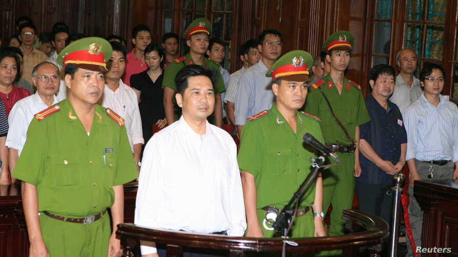 Cu Huy Ha Vu (C) stands between policemen in the dock during his trial at a court in Hanoi, August 21, 2011.