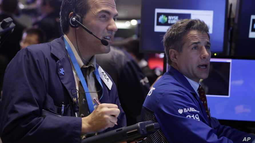Trader Gregory Rowe, left, and specialist Anthony Rinaldi work on the floor of the New York Stock Exchange, Oct. 7, 2013.