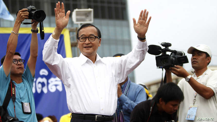 Sam Rainsy (C), president of the Cambodia National Rescue Party (CNRP), greets his supporters during the last day of a three-day protest at Freedom Park in Phnom Penh, Sept. 17, 2013.