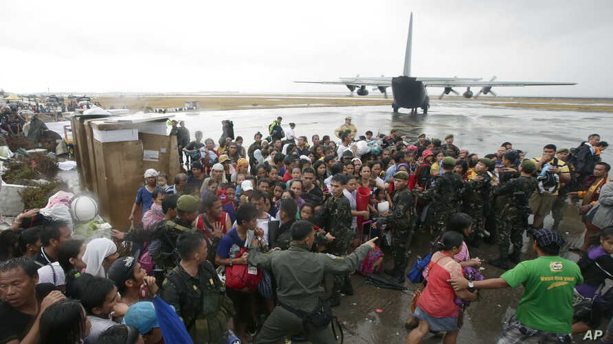 Typhoon survivors rush to get a chance to board a C-130 military transport plane in Tacloban city, Leyte province, central Philippines, Nov. 12, 2013.