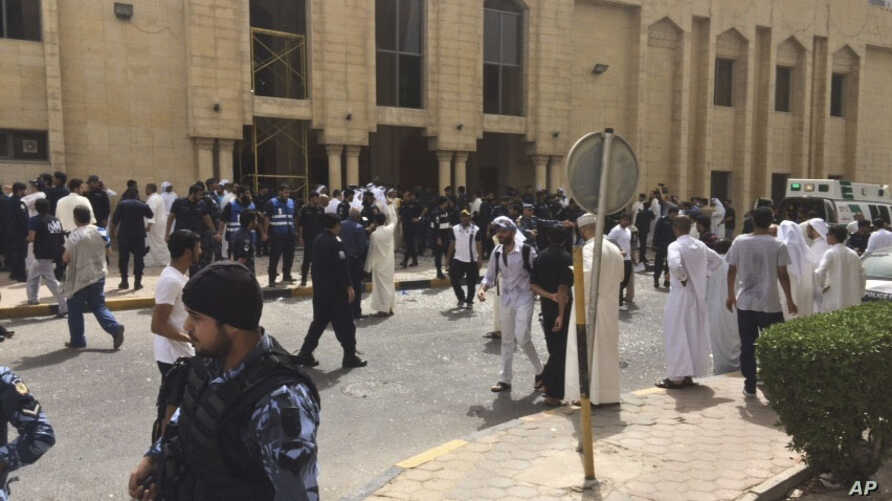 FILE - Security forces, officials and civilians gather outside of the Imam Sadiq Mosque after a deadly blast struck after Friday prayers in Kuwait City, Kuwait, June 26, 2015.