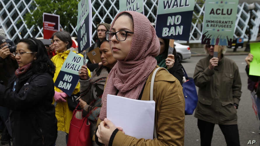 Isra Ayesh, center, of Seattle, who is the organizing director of Americans for Refugees and Immigrants, waits for her turn to speak during a demonstration against President Donald Trump's revised travel ban outside a federal courthouse in Seattle, M