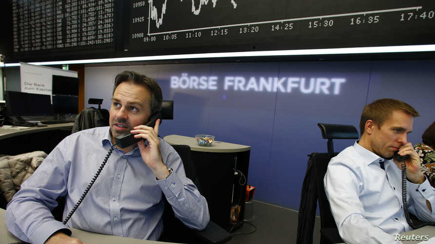 Traders work in front of the German share price index DAX board, at the stock exchange in Frankfurt, Germany, Nov. 4, 2015.