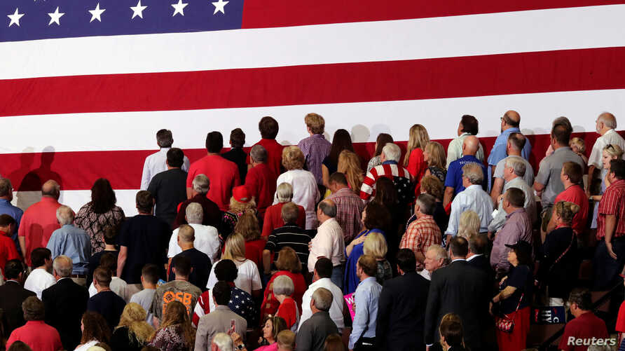 FILE - People turn to face a U.S. flag during the playing of the national anthem before U.S. President Donald Trump rallies with supporters during a Make America Great Again rally in Southaven, Mississippi, U.S. Oct. 2, 2018.