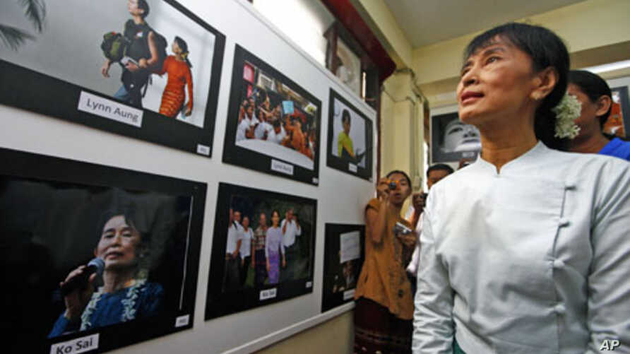 Burma's pro-democracy leader Aung San Suu Kyi looks at pictures of herself at a photo exhibition held at the National League for Democracy's office in Rangoon, Burma, May 23, 2011