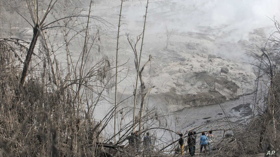 Villagers inspect the path of a pyroclastic flow from the eruption of Mount Sinabung in Gamber village, North Sumatra, Indonesia, May 22, 2016.