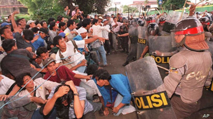 Indonesian students fall as riot policemen charge-in during an anti-government demonstration that turned violent at the gate of the Sahid University in Jakarta 29 April, 1998.  Clashes erupted as some 300 students who were demanding President Suharto