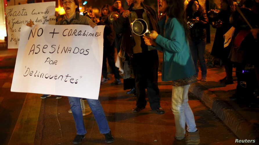 """A woman holds up a placard that reads """"No more policemen murdered by delinquents"""" as they beat cooking utensils during a rally against what participants say is an explosion in crime, Santiago, Chile, July 29, 2015."""